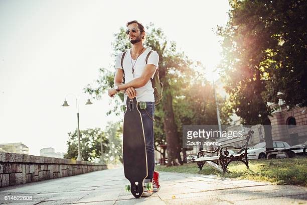 Hipster thinking while holding a longboard