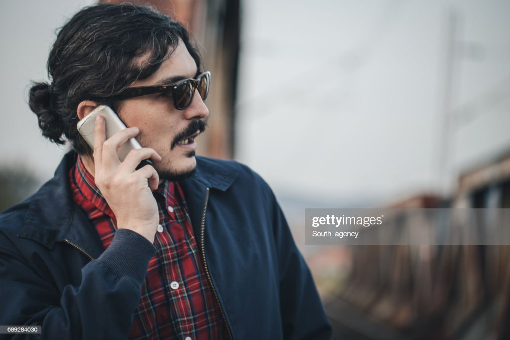 Hipster with a mobile phone : Stock Photo