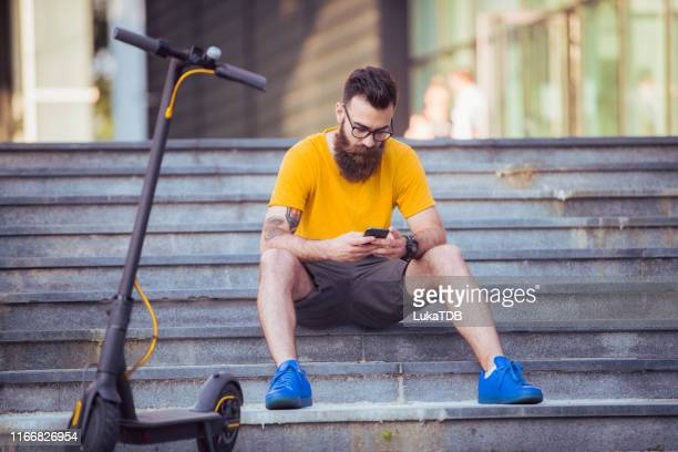 a hipster with an electric scooter typing on the phone - yellow shoe stock pictures, royalty-free photos & images