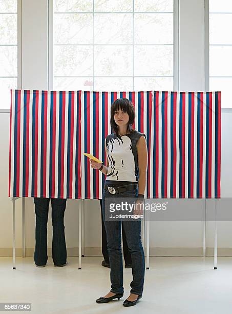 Hipster with ballot at voting booth
