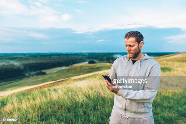 Hipster with beard uses smart phone outside in the country side