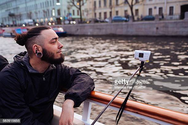 Hipster With Digital Camera Sailing In Ferry At City