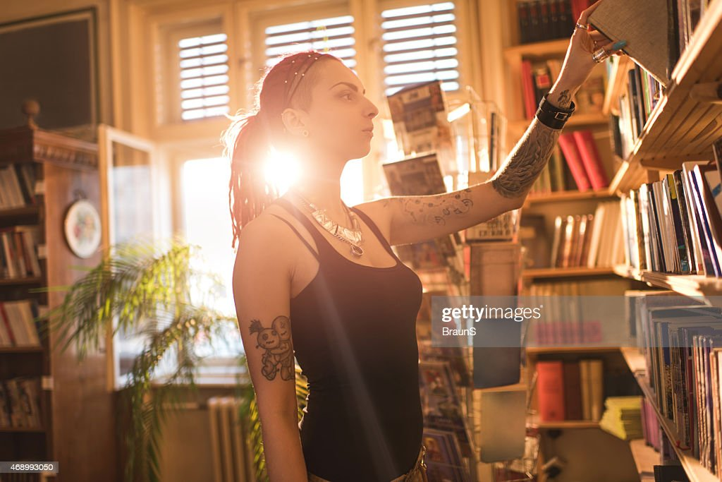 Hipster Woman Choosing A Book From Bookshelf In Library Stock Photo