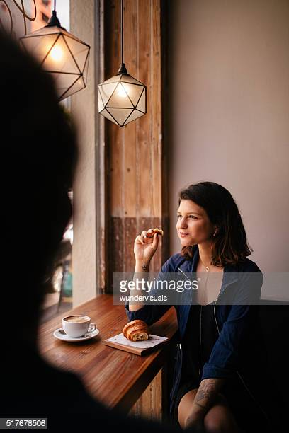Hipster Woman eats Croissant in Coffee Shop