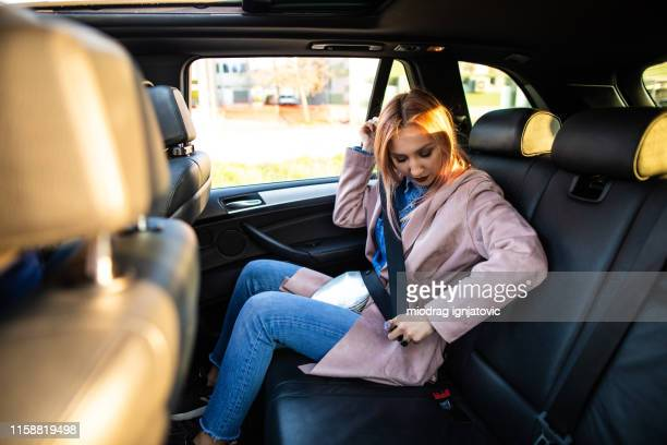 hipster woman fastening seat belt on back seat in car - fastening stock pictures, royalty-free photos & images