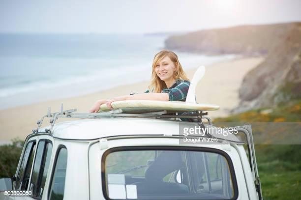 Hipster woman in car overlooking Atlantic coastline.