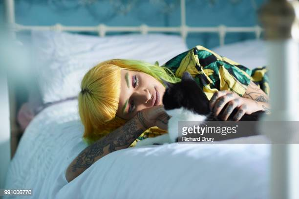 Hipster woman lying on her bed stroking her pet cat