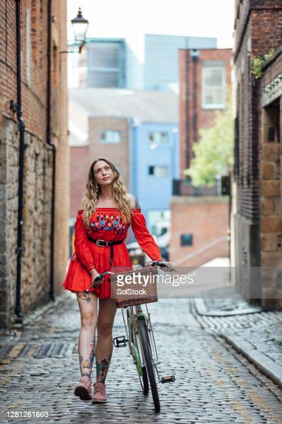 hipster woman pushing bicycle down cobbled street - two tone color stock pictures, royalty-free photos & images
