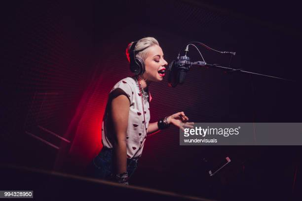 hipster woman recording rock music song in music recording studio - rap stock pictures, royalty-free photos & images