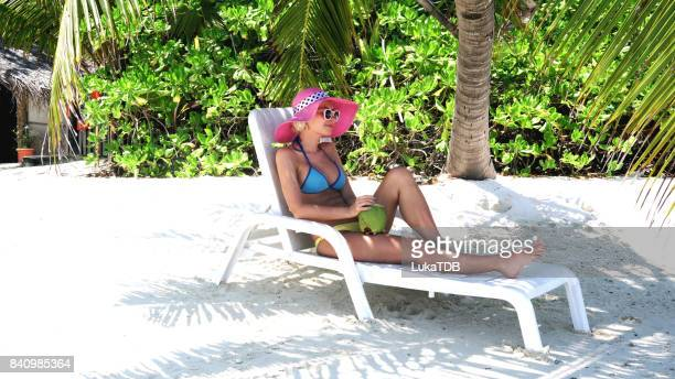 Hipster woman sitting and chilling on easy chair on beach, Maldives