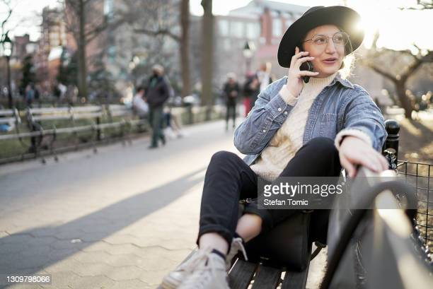hipster woman sitting outside on park bench and using phone at sunset - washington square park stock pictures, royalty-free photos & images