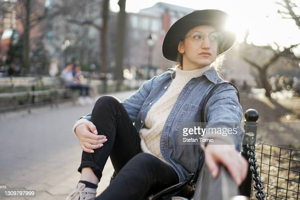 hipster woman sitting outside on park bench at sunset - washington square park stock pictures, royalty-free photos & images