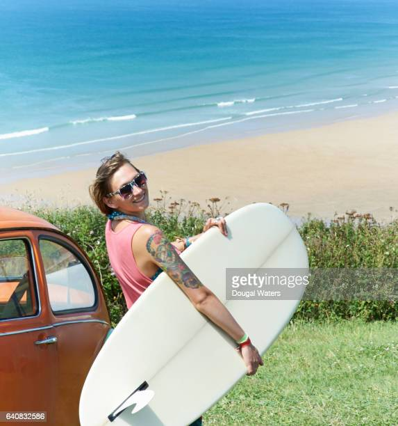 Hipster woman surfer with surf board and vintage car at beach.