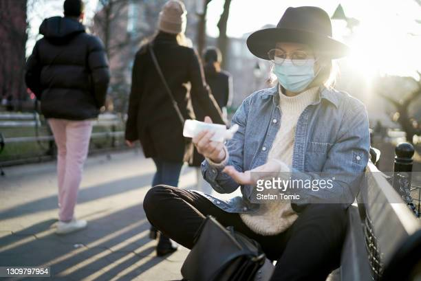 hipster woman using hand sanitizer while sitting outside on park bench at sunset - washington square park stock pictures, royalty-free photos & images