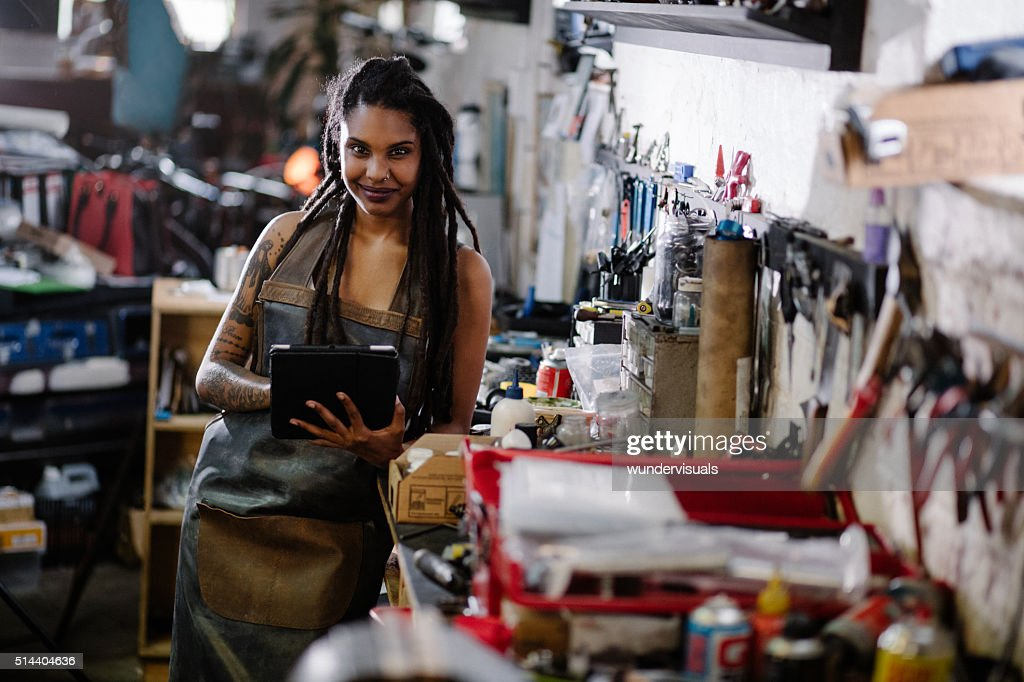 Hipster woman with digital tablet surrounded by tools in worksho : Stock Photo