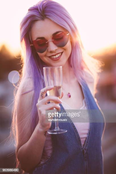 hipster woman with purple hair drinking champagne at summer party - pink hair stock pictures, royalty-free photos & images