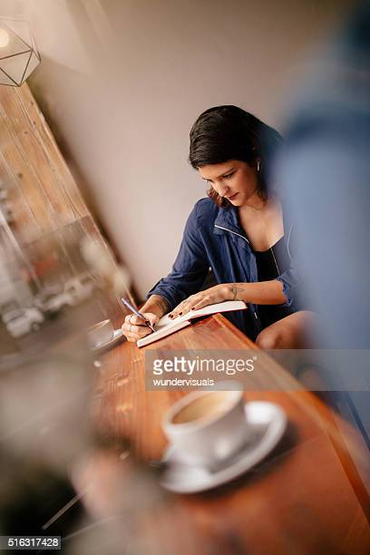 Hipster Woman Writing at Window Seat in Coffee Shop