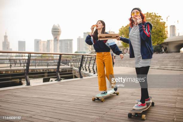 hipster women eating pizza and riding long boards - shanghai stock pictures, royalty-free photos & images