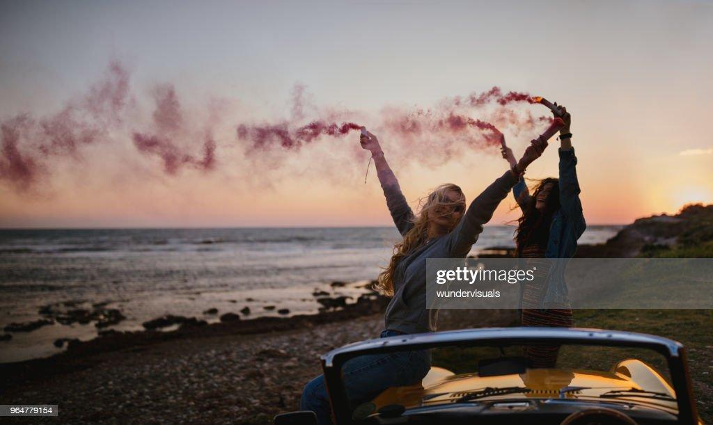 Hipster women having fun with smoke bombs at beach : Stock Photo