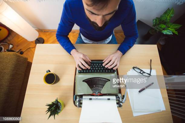 hipster writer working on typewriter - authors foto e immagini stock