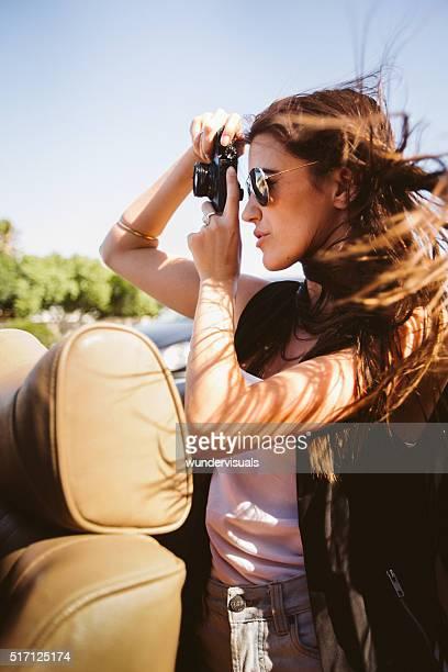 Hipster jeune adulte femme prenant une photo de la voiture décapotable