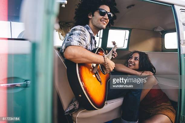 Hipster junger Erwachsener Mann spielt Gitarre für seine Freundin