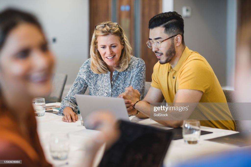 Hipster young man showing female colleague laptop : Stock Photo