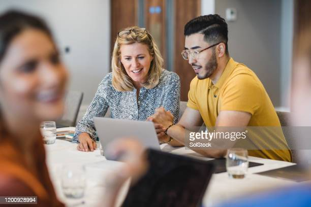hipster young man showing female colleague laptop - multi ethnic group stock pictures, royalty-free photos & images