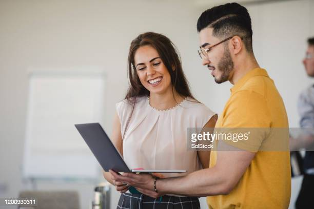 hipster young man using laptop with cheerful female colleague - coworker stock pictures, royalty-free photos & images