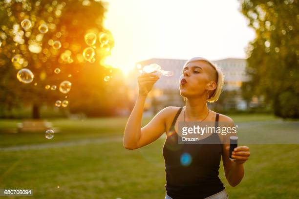 hipster young woman in park on sunny summer day, relaxing and enjoying sun - half shaved hairstyle stock photos and pictures