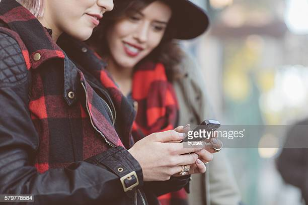 Hipster young women using smart phones outdoor on city street