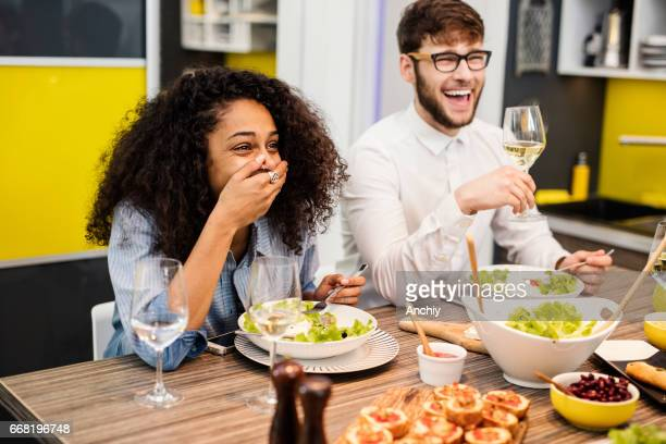 Hipsters laughing while eating salad.