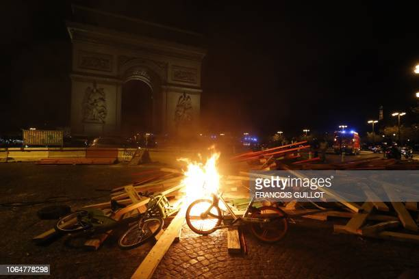 Hire bicycles lie on burning material during a rally by yellow vest protestors against rising oil prices and living costs as night falls near The Arc...