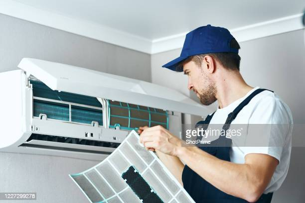 a hired worker repairman cleans and repairs the air conditioner. - bouche d'aération photos et images de collection