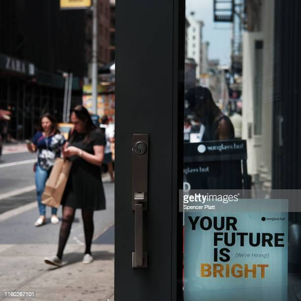 A hiring sign is displayed in a business window along a shopping street in lower Manhattan on July 05 2019 in New York City According to the latest...