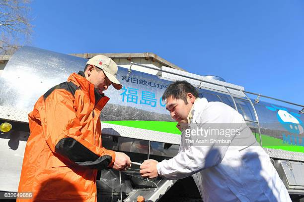Hiroaki Hiruta exchanges business cards with an official who came to pick up raw milk from the Hiruta dairy farm on January 24 2017 in Naraha...