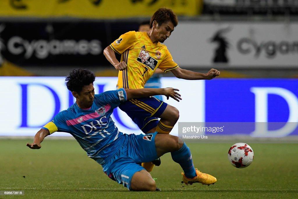 Hiroaki Okuno of Vegalta Sendai is tackled by Yohei Toyoda of Sagan Tosu during the J.League J1 match between Sagan Tosu and Vegalta Sendai at Best Amenity Stadium on June 17, 2017 in Tosu, Saga, Japan.