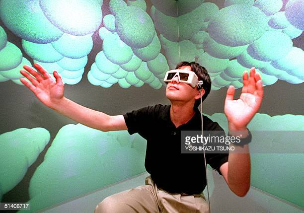 Hiroaki Yano a researcher of the Tokyo University's Intelligent Modeling Laboratory with a 3D glasses extends his hands to touch carbon atoms as he...