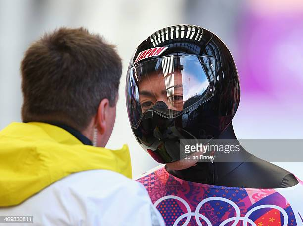 Hiroatsu Takahashi of Japan talks with his coach after competing a run during the Men's Skeleton heats on Day 7 of the Sochi 2014 Winter Olympics at...