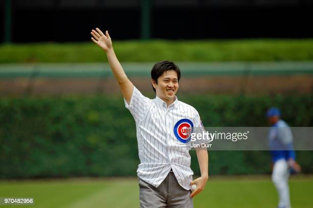 Hirofumi Yoshimura mayor of Osaka Japan acknowledges the crowd before throwing out a cermonial first pitch before the game between the Chicago Cubs...