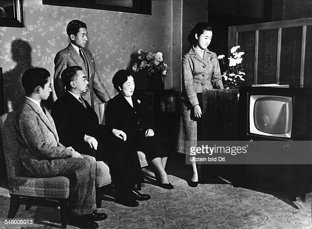 Hirohito Emperor of Japan surrounded by his family in the Imperial Palace in Tokyo the Imperial family infront of the US TV from left to right Prince...
