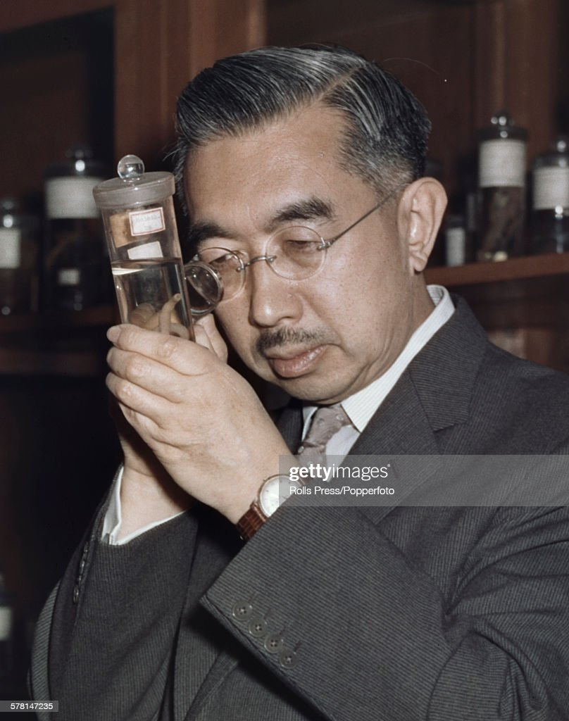 Hirohito, Emperor Showa of Japan (1901-1989) pictured studying a marine biology specimen through an eyeglass in a laboratory circa 1965.