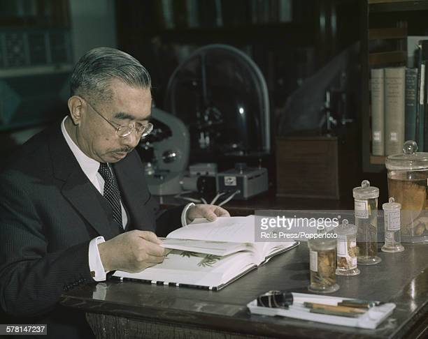Hirohito Emperor Showa of Japan pictured studying a marine biology textbook in a laboratory circa 1965