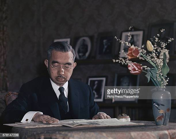 Hirohito Emperor Showa of Japan pictured studying a newspaper at a table circa 1965