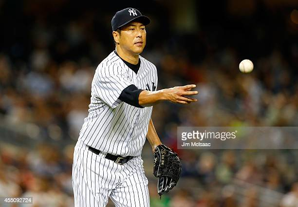 Hiroki Kuroda of the New York Yankees flips the ball to first base for the final out of the third inning against the Tampa Bay Rays at Yankee Stadium...