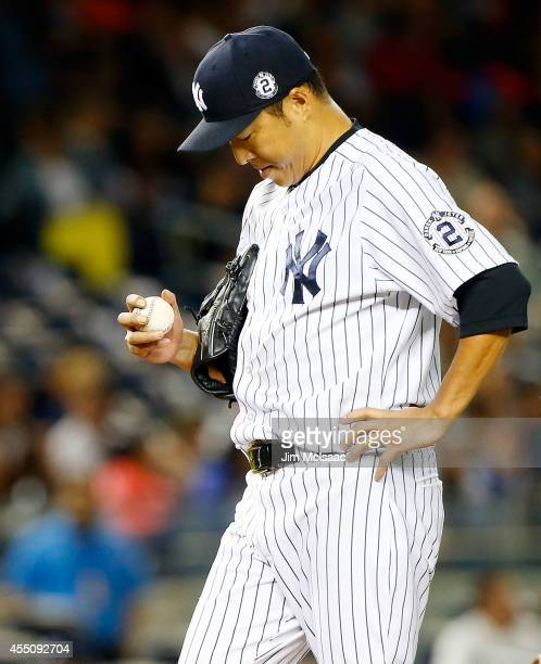 Hiroki Kuroda of the New York Yankees stands on the mound in the fourth inning before leaving the game against the Tampa Bay Rays at Yankee Stadium...