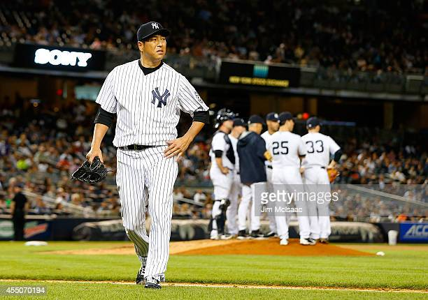 Hiroki Kuroda of the New York Yankees walks to the dugout as he leaves a game against the Tampa Bay Rays in the fourth inning at Yankee Stadium on...