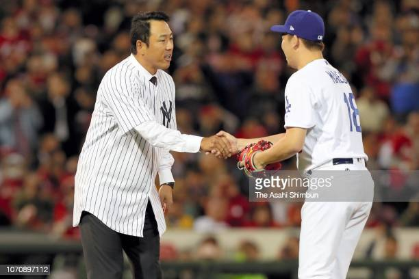 Hiroki Kuroda shakes hands with Kenta Maeda of the Los Angeles Dodgers after throwing the ceremonial first pitch prior to the game four between Japan...