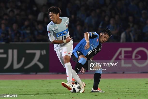 Hiroki Miyazawa of Consadole Sapporo and Hiroyuki Abe of Kawasaki Frontale compete for the ball during the JLeague J1 match between Kawasaki Frontale...