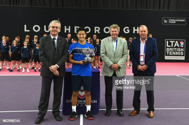 Hiroki Moriya of Japan poses with the Loughborough Trophy after winning the Mens Singles Final with Professor Chris Linton Provost and Deputy Vice...